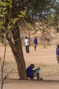 Oblivious to the new footballs getting a work out. The impact on this young man of a simple exercise book and pen brought a tear to my eye! Photo by Stephen Powell Wildlife Artist.